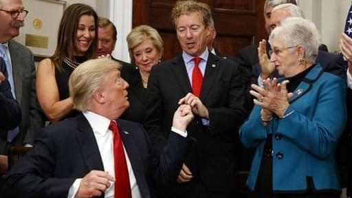 President Donald Trump hands a pen that he used to sign an executive order on health care to Sen. Rand Paul, R-Ky., in the Roosevelt Room of the White House on Thursday.