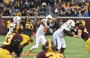 Illinois quarterback Cam Thomas stiff arms Minnesota defensive back Duke McGhee as he rushes for a first down.