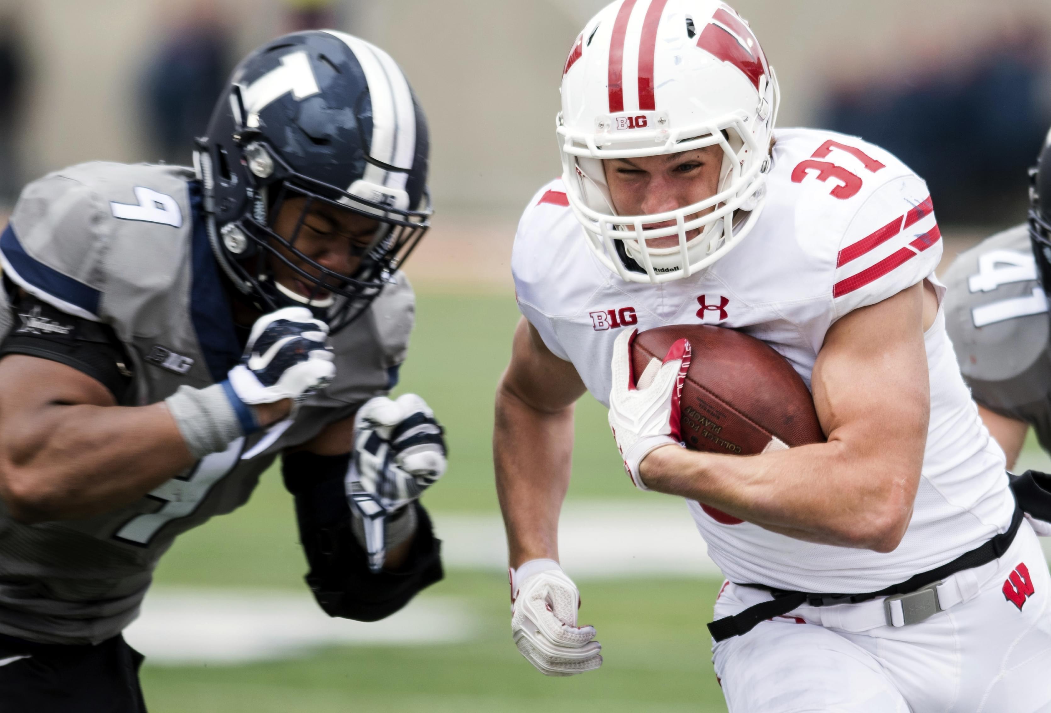 Wisconsin running back Garrett Groshek tries to avoid a tackle by Illinois linebacker Dele Harding.