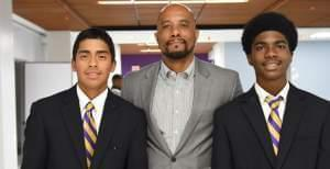 Principal standing with two male students