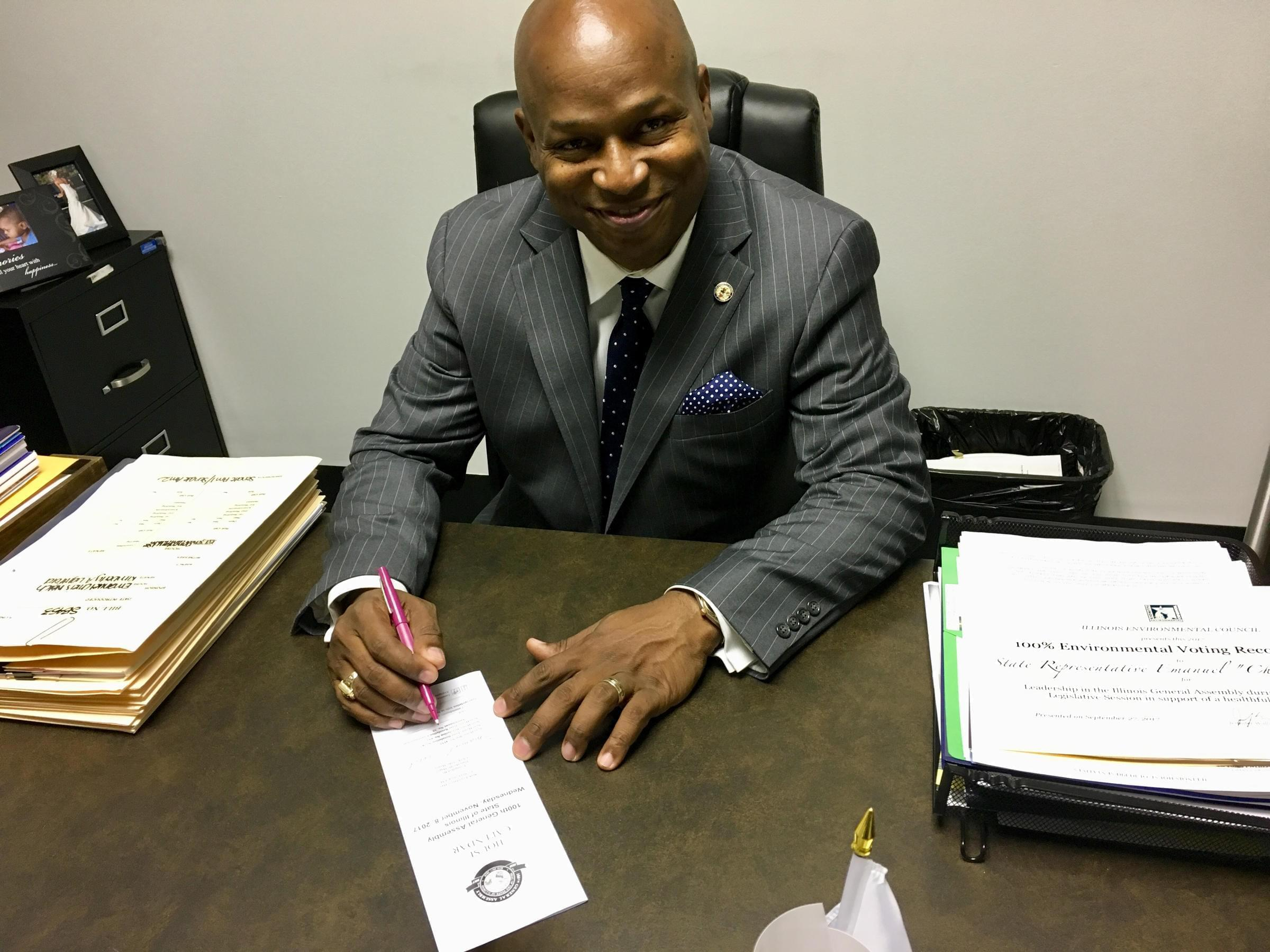 State Rep. Emanuel Chris Welch demonstrates his own penmanship on the House calendar after his cursive bill became law.