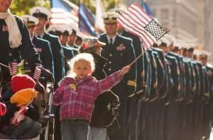 Blond little girl waving a small American flag at a Veteran's Day parade