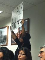 A woman holds a sign during a Champaign County Board meeting in October of 2015.