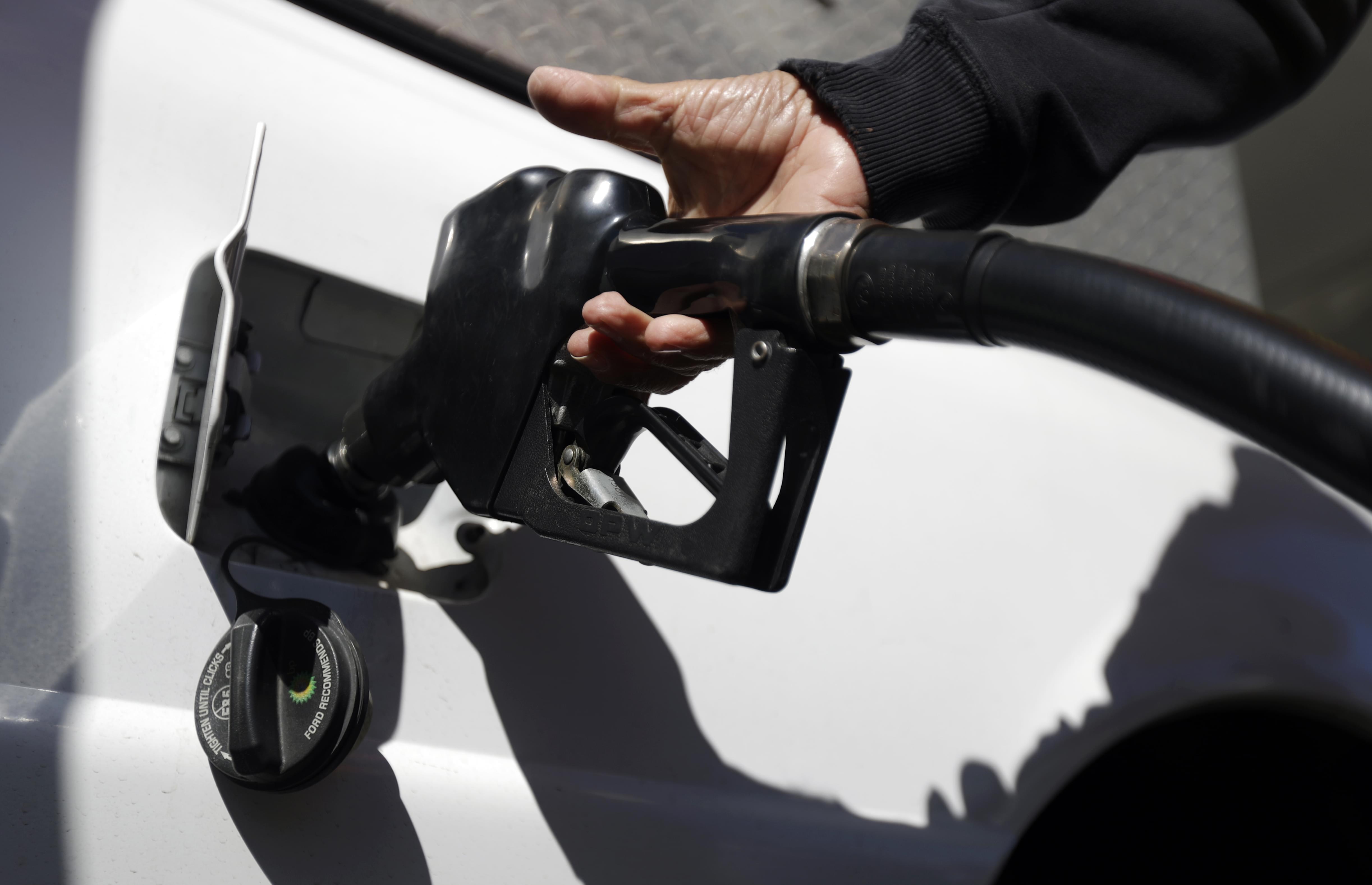 A person pumps gas into their car.