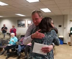 Champaign County Treasurer Dan Welch receives a hug from County Board member Diane Michaels.
