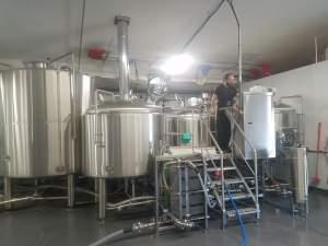 An employee tends to brewing equipment at the Riggs Brewing Company in Urbana.