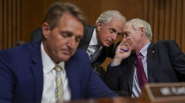 Sens. Jeff Flake, R-Ariz., Bob Corker, R-Tenn., and Ron Johnson, R-Wis., seen at a hearing earlier this month, held up floor action on Thursday evening over concerns about how to control the deficit if the GOP tax bill doesn't result in strong e