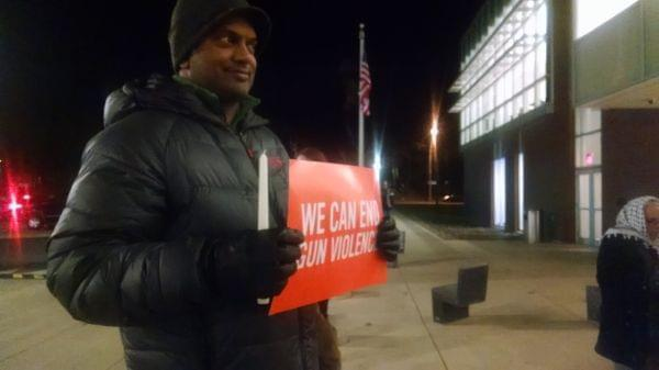 Man holding sign demanding strict gun control legislation