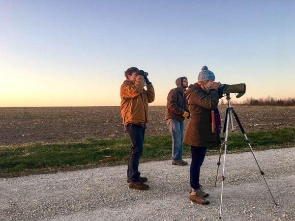 Three people dressed for cold stand on a gravel road through a bare winter field looking into the distance through binoculars and a spotting scope.