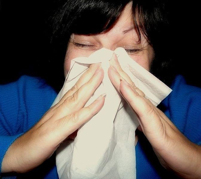 A woman sneezing into a hankerchief.