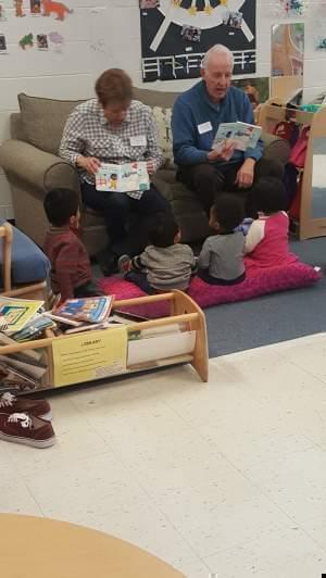 2 volunteers reading to small children