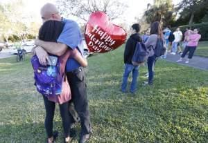 Family members, one of them holding a heart-shaped Valentine's Day balloon, embrace following a shooting at Marjory Stoneman Douglas High School, in Parkland, Florida on Wednesday.
