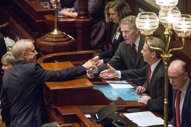 Gov. Bruce Rauner shakes hands with House Speaker Michael Madigan, left, and Senate President John Cullerton.