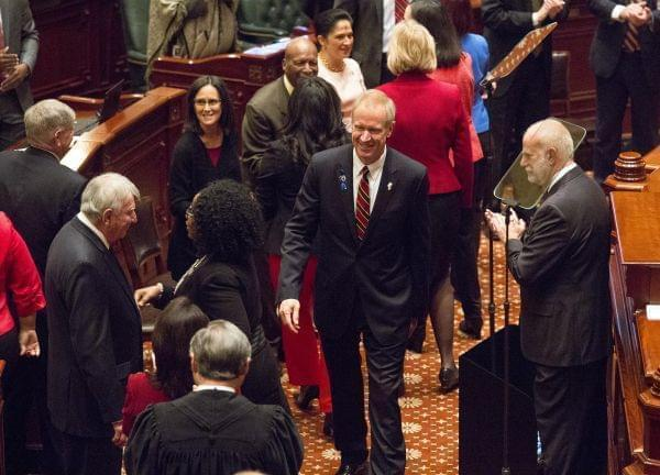 Gov. Bruce Rauner greets Illinois officials before his annual budget address Wednesday.