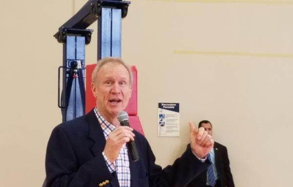 Gov. Bruce Rauner talks to employees at the Litania Sports Group athletic equipment company in Champaign.