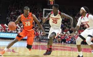 Illinois' Damonte williams drives against Rutgers defenders Issa Thiam (35) and Deshawn Freeman