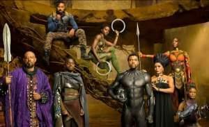Main characters from the movie Black Panther standing together in African attire on the side of a mountain cliff.