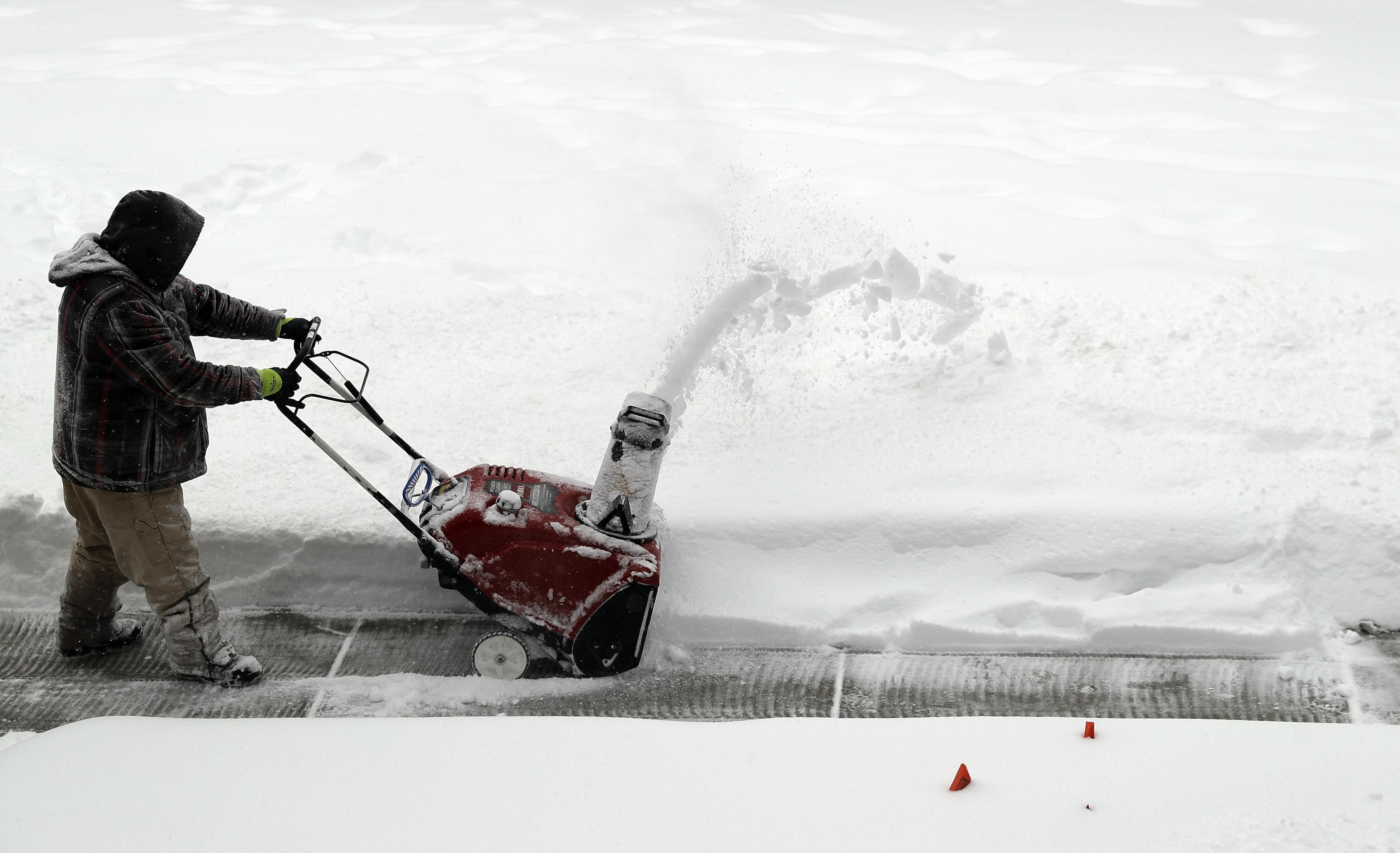 A man uses a snowblower to clear snow from a sidewalk in Chicago during a February snowstorm.