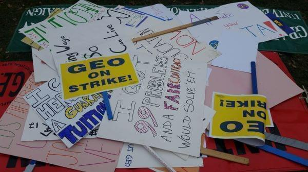 Posters and signs with strike slogans written on them. Signs are part of the GEO strike on the University of Illinois Urbana-Champaign campus.