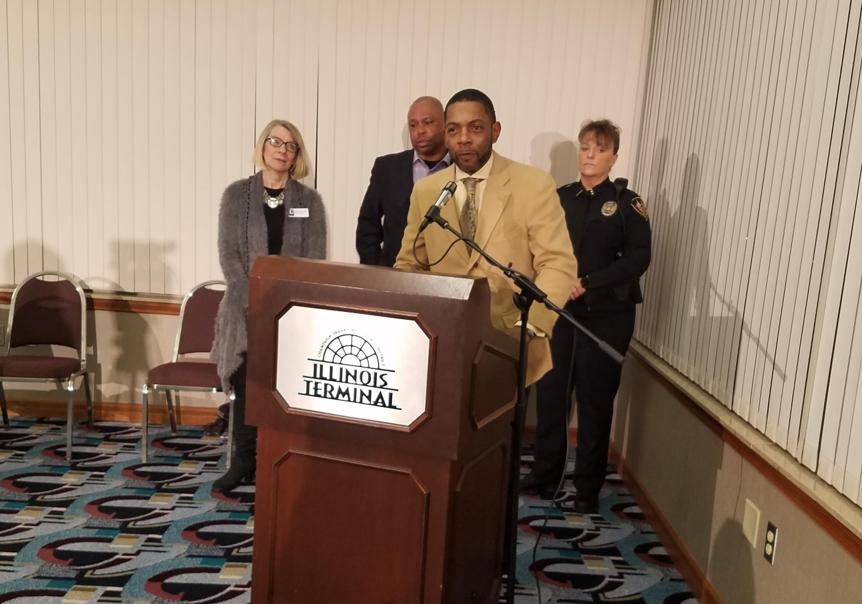 Champaign barber and funeral director Seon Williams, flanked by Urbana Mayor Diane Marlin, Tracy Parsons with the city of Champaign, and Urbana Police Chief Sylvia Morgan.