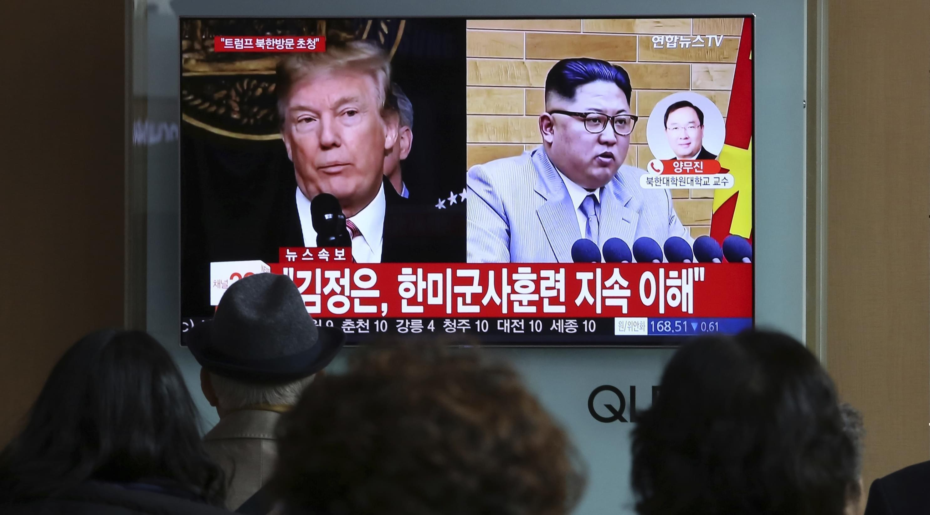 """People watch a TV screen showing North Korean leader Kim Jong Un and U.S. President Donald Trump at the Seoul Railway Station in Seoul, South Korea, Friday, March 9.The headlines on the TV screen reads: """" Kim Jong Un understands that the routine"""