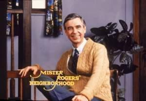 PBS icon, Fred Rogers seated with his toy trolley.
