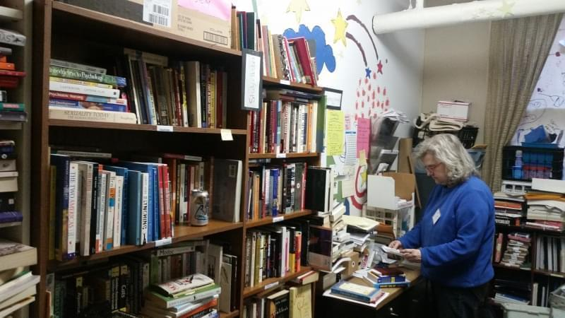 Vicki White, president of Chicago Books to Women in Prison, reads a letter sent from an incarcerated woman. She is standing in a room lined with bookcases and book shelves full of books.