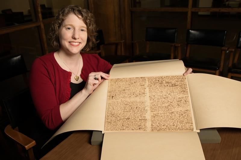 Lynne Thomas poses with Isaac Newton manuscript.