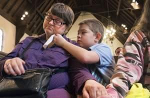 Nicholas Weible, offers his mom, Wendy Smith a tissue during the memorial service for his father, Christopher Weible, held at First Christian Church in Quincy, on April 20.