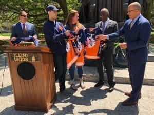 Illini 4000 Board Members present Chancellor Robert Jones and other campus administrators with bicycle gear for when they take part in one day of the Illini 4000 in the Champaign-Urbana area.
