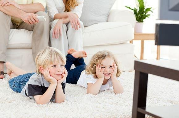 2 small children laying on floor watching tv. Parents are seated on couch.