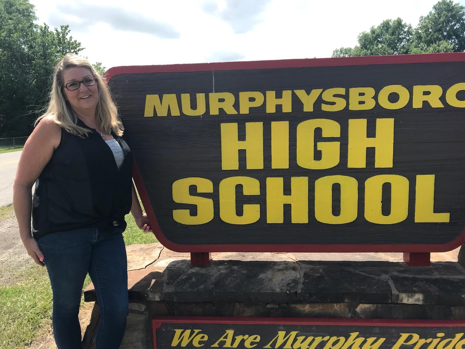 Murphysboro High School teacher Stacie Tefft stands next to a sign for the high school.