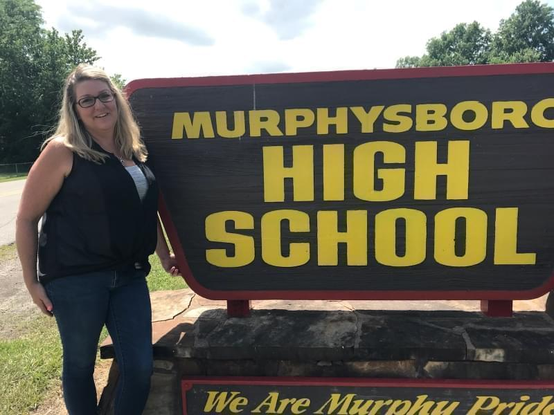 Murphysboro High School teacher Stacie Tefft stands next to a sign for the high school.