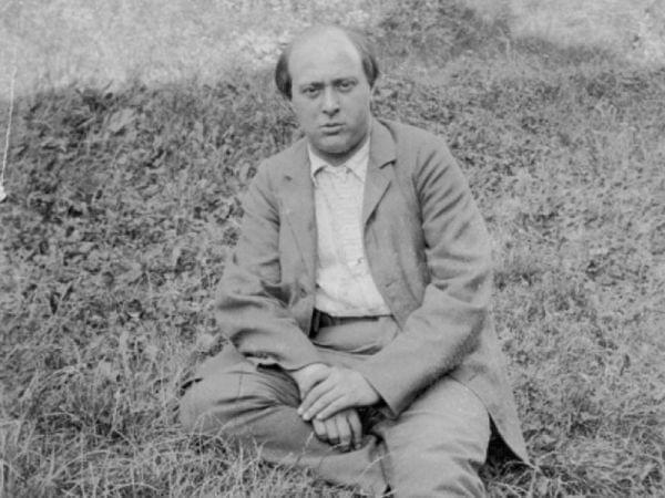 Composer Arnold Schönberg sitting on ground