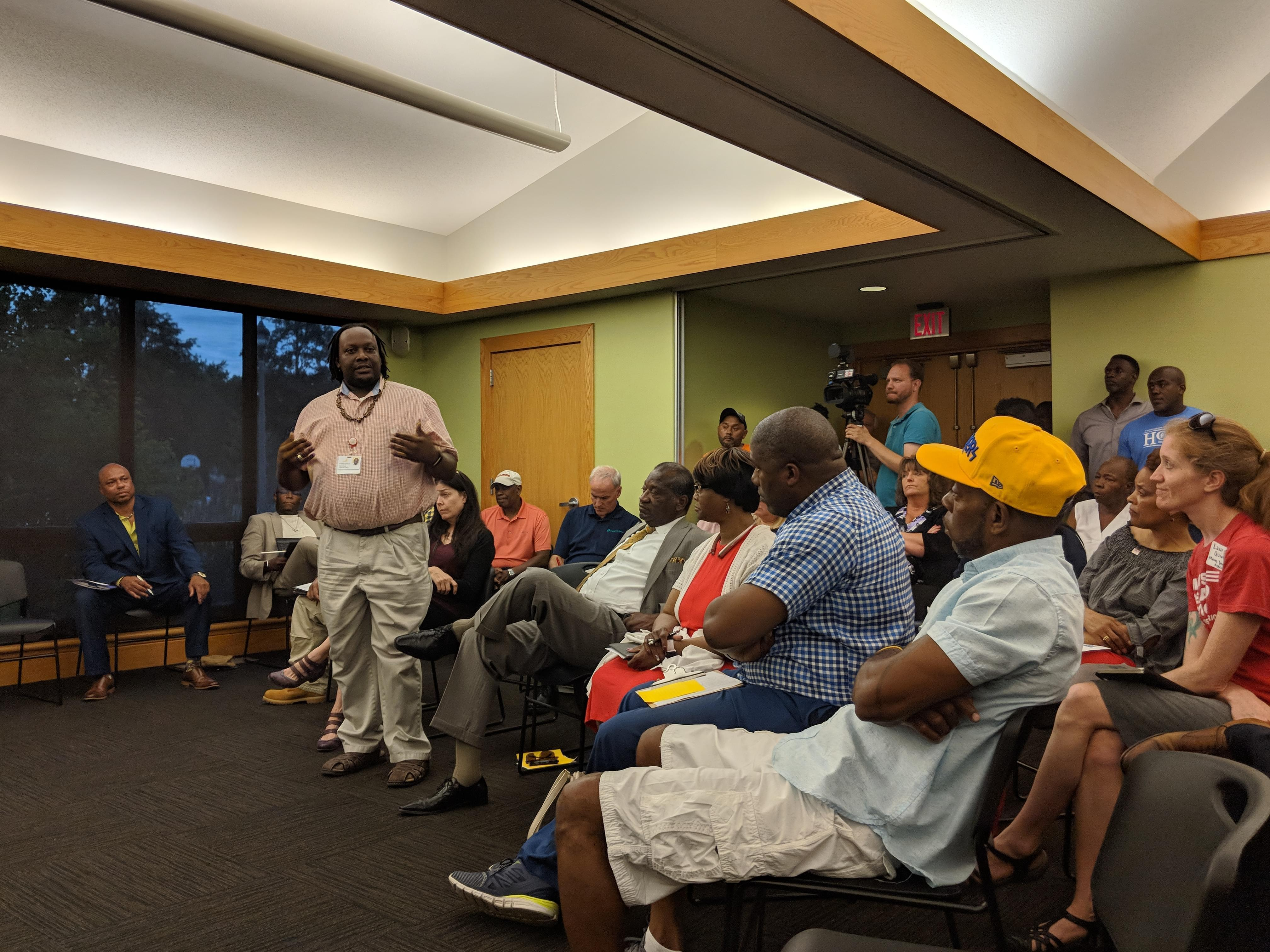 Donte' Lotts of CU Fresh Start speaks in front of a crowd of people at the Douglass branch library.
