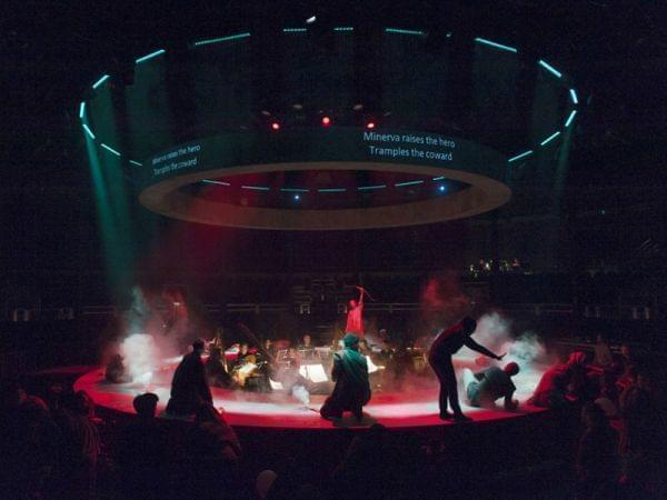 people perform on a round stage with orchestra in the middle