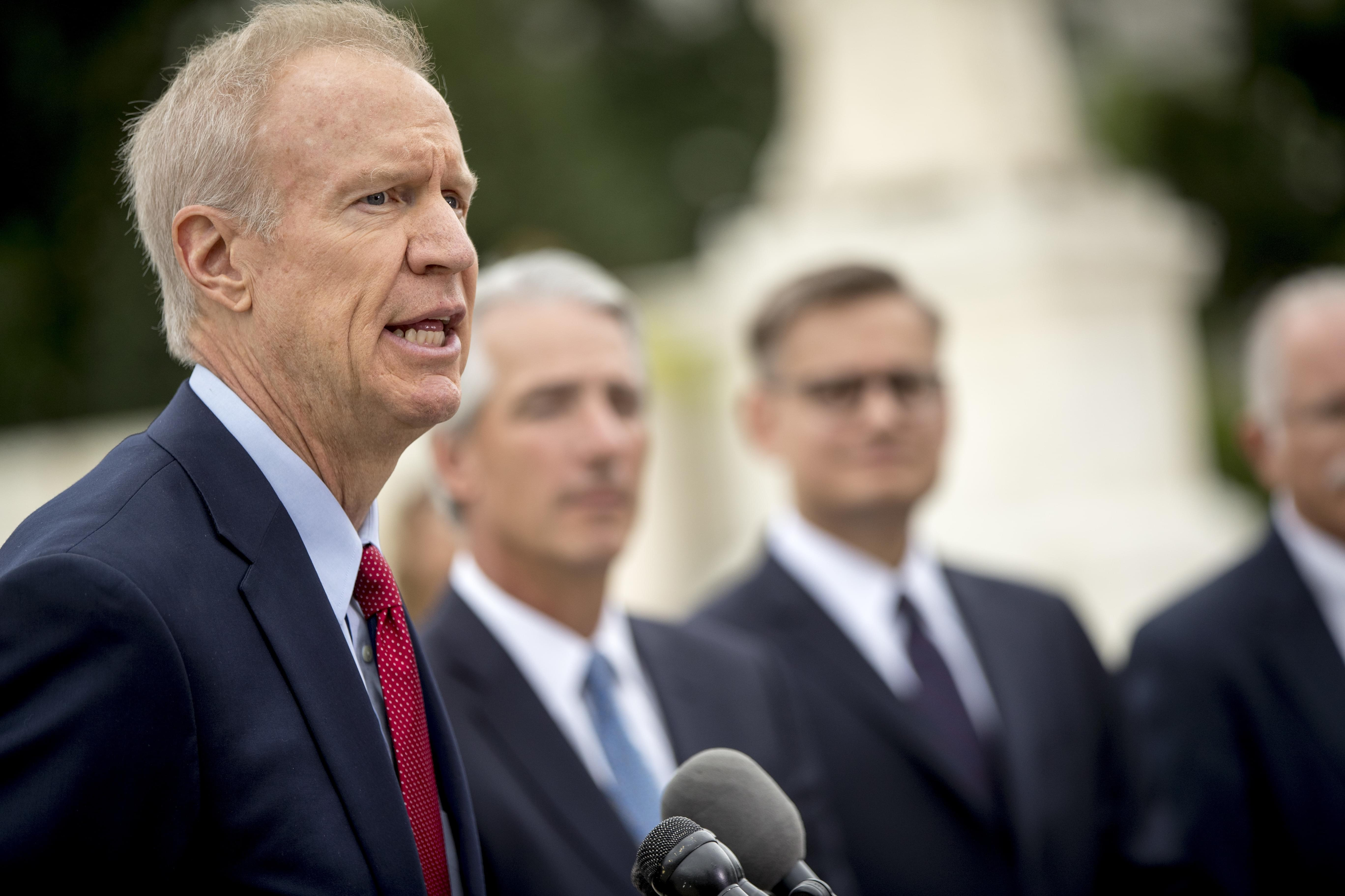 Illinois Gov. Bruce Rauner, left, accompanied by Liberty Justice Center founder and chairman John Tillman, second from left, and Liberty Justice Center's Director of Litigation Jacob Huebert, right, speaks outside the Supreme Court after the cou