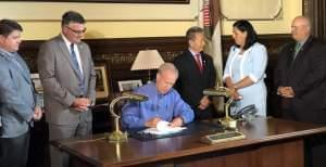 Gov. Bruce Rauner signing legislation.