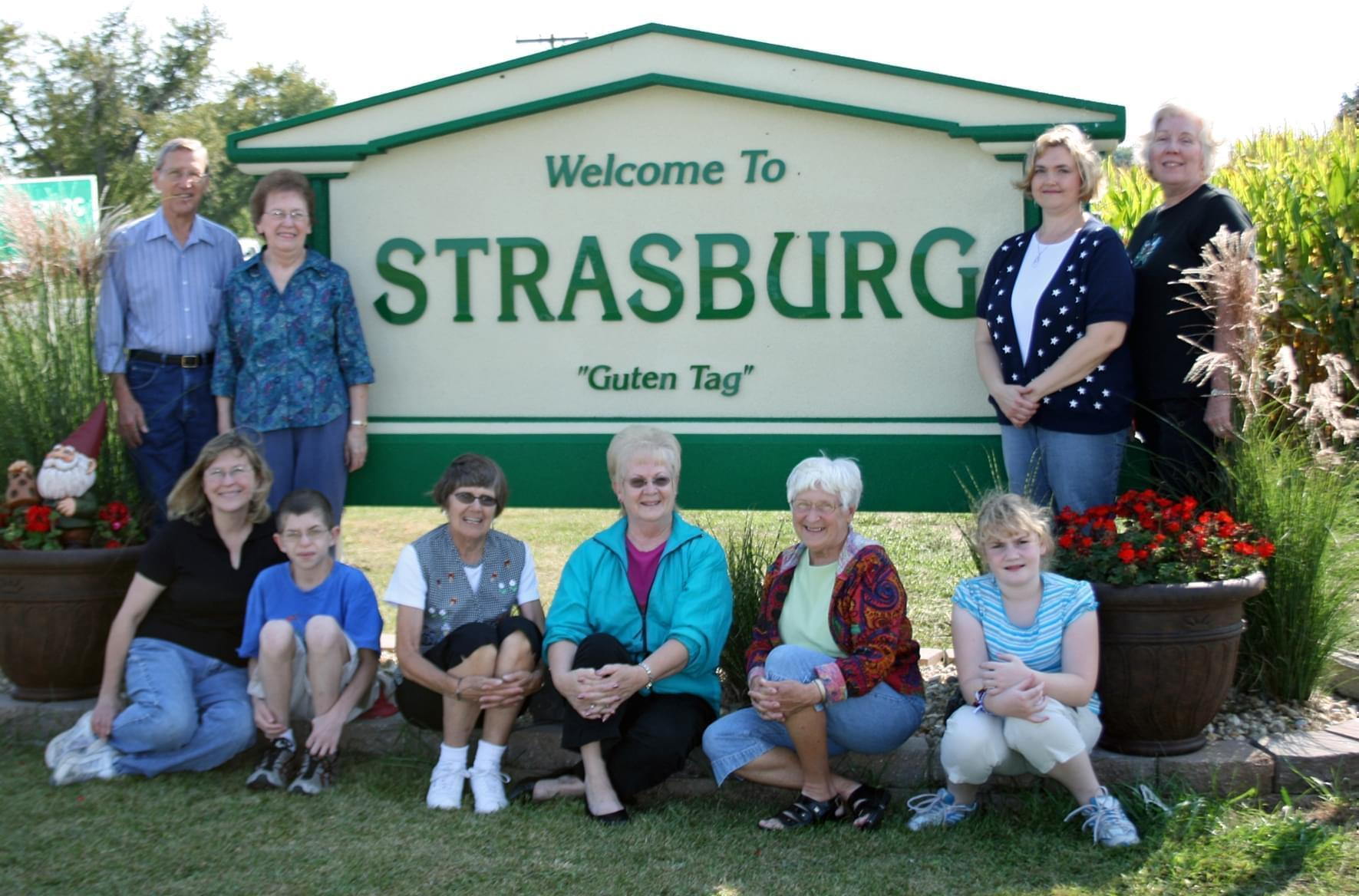 Residents gathered around Strasburg welcome sign.