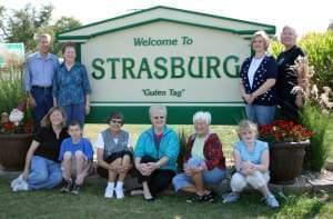 Residents gathered around Strasburg welcome sign.
