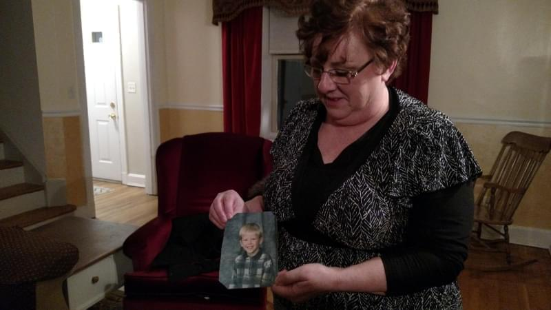 Toni Hoy holds a picture of her son, Daniel, at her home in Rantoul, Illinois. In a last-ditch effort to get Daniel treatment for his severe mental illness, they gave him up to the state in 2008, when he was 12.