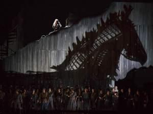 Woman sits atop a stage overlooking crowd and a metal trojan horse
