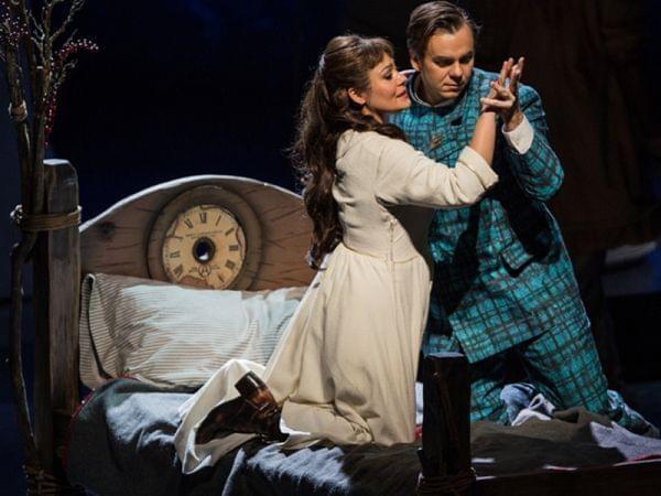 A man and woman embrace on a bed on a stage