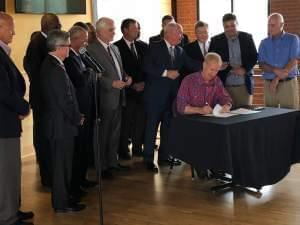 Gov. Bruce Rauner signs legislation surrounded by public university presidents at Papa Del's Pizza in Champaign.