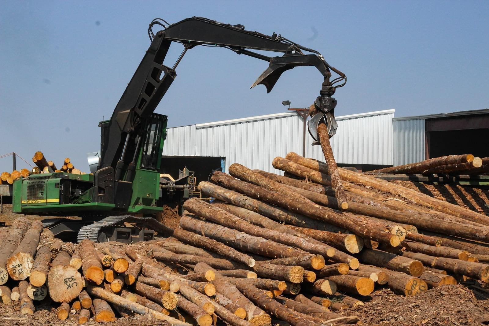 A machine piles pine logs for processing at the Montrose Forest Products sawmill. In 2012, this Colorado log yard was nearly empty.
