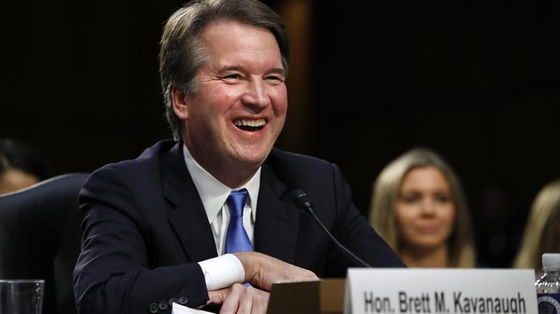 Supreme Court nominee Brett Kavanaugh laughs as closing remarks are made Wednesday evening after the second day of his confirmation hearings before a Senate panel on Capitol Hill in Washington, D.C., to replace retired Justice Anthony Kennedy.