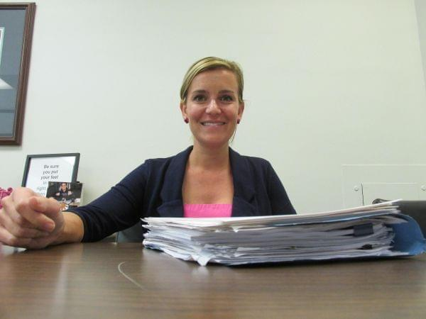 State Rep. Sara Wojcicki Jimenez sits behind a stack of reports and findings related to the House Sexual Discrimination and Harassment Task Force.