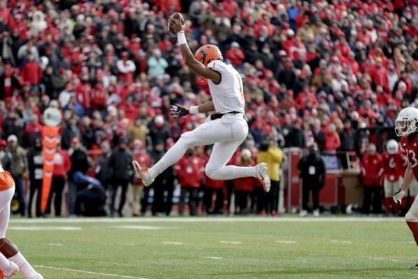 Illinois quarterback AJ Bush Jr leaps inito the end zone for a touchdown.