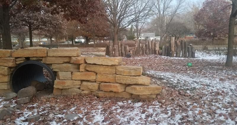 The hill-and-tunnel and the log wall at the Friendship Grove Nature Playscape in Urbana.
