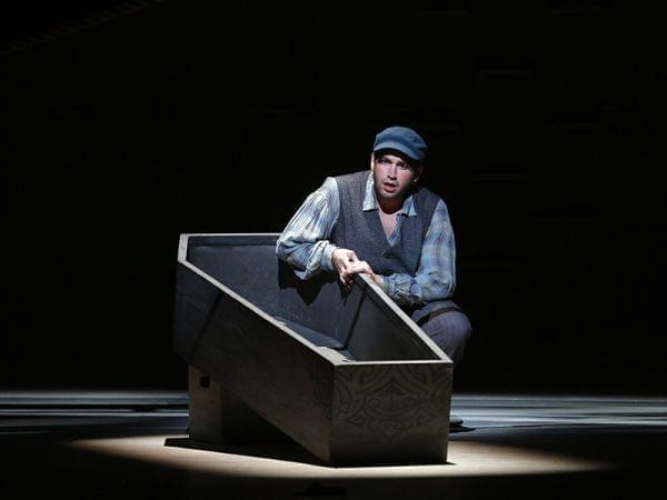 Man is along on stage with a coffin.